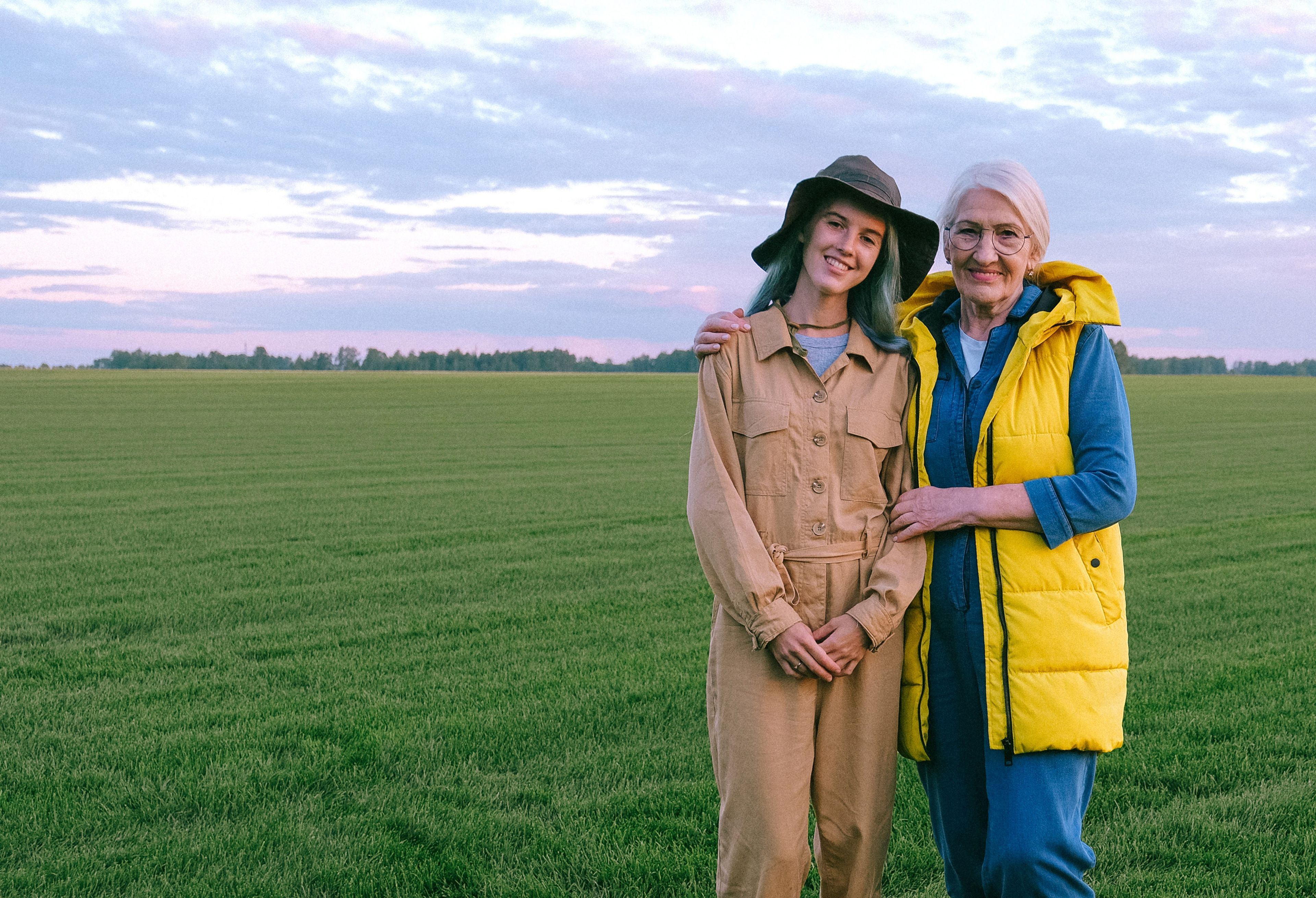 A young lady and older lady standing in a field